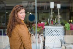 Portrait of smiling woman in front of window looking at camera. At the shopping mall Royalty Free Stock Photo