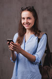 Portrait of smiling woman with glasses and cellphone near grey background wall. Closeup portrait of beautiful happy young woman with glasses chats by cellphone stock images