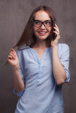 Portrait of smiling woman with glasses speaking by cellphone near grey background wall. Closeup portrait of beautiful happy young woman with glasses speaking by Royalty Free Stock Images