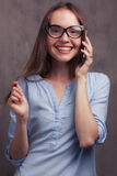 Portrait of smiling woman with glasses speaking by cellphone near grey background wall. Closeup portrait of beautiful happy young woman with glasses speaking by Royalty Free Stock Photography