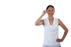 Portrait of smiling woman with hand on hip adjusting invisible eyeglasses Stock Image