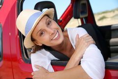 Portrait of smiling woman with hat looking out of car window Stock Images