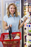Portrait of smiling woman having on her hands a fresh milk bottle and shopping basket Royalty Free Stock Photos