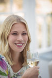 Portrait of smiling woman having wine during lunch Stock Image
