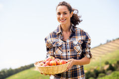 Portrait of smiling woman holding apple basket Stock Photos