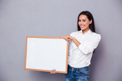 Portrait of a smiling woman holding blank board Stock Photos