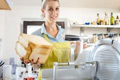 Smiling woman holding bread loaf in kitchen. Portrait of a smiling woman holding bread loaf in kitchen royalty free stock photography