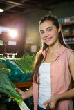 Portrait of smiling woman holding bunch of scallions in organic section Stock Photo