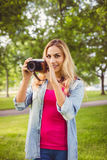 Portrait of smiling woman holding camera in park Stock Photo