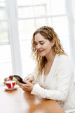 Smiling woman using smart phone Royalty Free Stock Photography