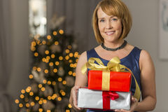 Portrait of smiling woman holding Christmas presents at home Royalty Free Stock Images