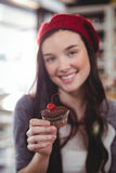 Portrait of smiling woman holding cupcake Stock Image