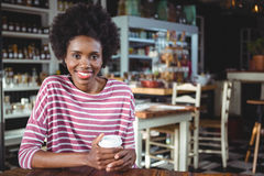 Portrait of smiling woman holding disposable coffee cup Stock Photography