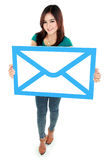 Portrait of smiling woman holding envelope sign Stock Photos