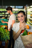 Portrait of smiling woman holding a grocery bag in organic section Stock Image