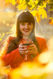 Portrait of smiling woman holding hot of tea at autumn park Stock Photos