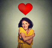 Portrait smiling woman holding hugging herself with red heart above head Royalty Free Stock Photos
