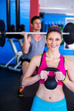 Portrait of smiling woman holding kettlebell with man lifting weights Stock Image