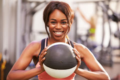 Portrait of a smiling woman holding a medicine ball at a gym Royalty Free Stock Photos