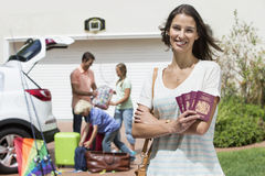 Portrait of smiling woman holding passports in driveway with family packing car in background. Portrait of smiling women holding passports in driveway with royalty free stock images