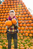 Portrait of smiling woman holding pumpkins in autumn outdoors Stock Photos