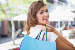 Portrait of smiling woman holding shopping bag and looking over the shoulder at camera Stock Photo