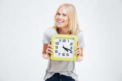 Portrait of a smiling woman holding wall clock Royalty Free Stock Photo