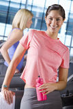 Portrait of smiling woman holding water bottle on treadmill in health club. Portrait of smiling women holding water bottle on treadmill in health club Royalty Free Stock Photography
