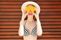 Portrait smiling woman holds in hands oranges and hides his eyes Royalty Free Stock Images