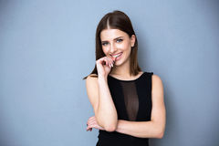 Portrait of a smiling woman in hot dress. Standing over gray background Royalty Free Stock Photo