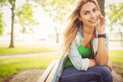 Portrait of smiling woman with legs crossed at park Royalty Free Stock Images