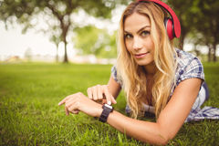 Portrait of smiling woman listening to music and touching wristwatch Royalty Free Stock Photos