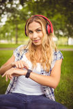 Portrait of smiling woman listening to music and using smartwatch Stock Photo