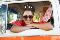 Portrait of smiling woman looking through camper van window Stock Images