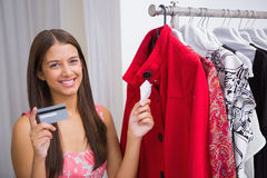 Portrait of smiling woman looking at red coat and holding credit card Stock Photography