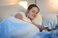 Portrait of smiling young woman lying in bed and reading book on digital tablet before going to sleep royalty free stock image