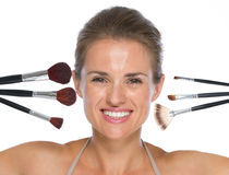Portrait of smiling woman with makeup brushes Royalty Free Stock Photography