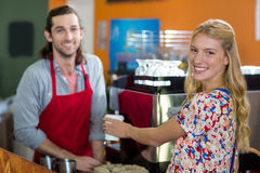 Portrait of smiling woman and male staff at café counter. Portrait of smiling women and male staff at café counter in supermarket Stock Images
