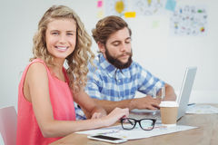 Portrait of smiling woman with man working on laptop Stock Images