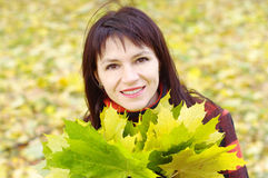 Portrait of smiling woman with maple leaves in autumn Royalty Free Stock Images