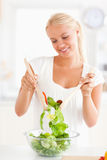 Portrait of a smiling woman mixing a salad Royalty Free Stock Photo