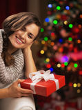 Portrait of smiling woman near christmas tree holding present box Royalty Free Stock Photos