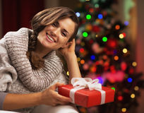 Portrait of smiling woman near christmas tree with present box Stock Image
