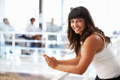Portrait of smiling woman in office with smart phone Royalty Free Stock Images