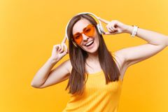 Portrait of smiling woman in orange glasses listening music in headphones copy space isolated on yellow background royalty free stock photos