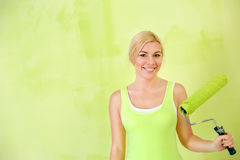 Portrait of smiling woman with paint roller Stock Images