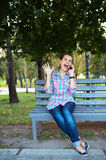 A portrait of a smiling woman in a park on a bench talking on th Royalty Free Stock Image