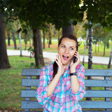 A portrait of a smiling woman in a park on a bench talking on th Royalty Free Stock Photography