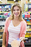 Portrait of a smiling woman paying at cash register paying with credit card Stock Images