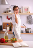 Portrait a smiling woman with phone  in kitchen at Royalty Free Stock Image